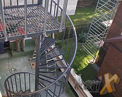 Schody kręcone ze stopniami z kraty, balustrada z dwoma tralkami na stopniu i poręczą giętą stalową. Schody zostały zamontowane w Warszawie.