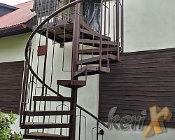 Schody kręcone ze stopniami z deski tarasowej, balustrada standardowa, cynkowane i malowane proszkowo. Las