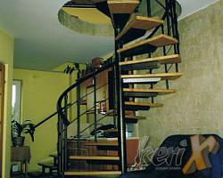 """Schody kręcone, stopnie bukowe lakierowane w kolorze naturalnym, balustrada z trzema prętami, poręcz stalowa gięta. Elementy stalowe malowane proszkowo w kolorze """"antyczne złoto"""". Wykonanie- Pisarzowice, woj. śląskie."""