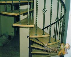 """Schody kręcone, stopnie bukowe lakierowane w kolorze naturalnym, balustrada kuta, poręcz stalowa gięta. Elementy stalowe malowane proszkowo w kolorze """"antyczne złoto"""".  Wykonanie- Częstochowa, woj. śląskie."""